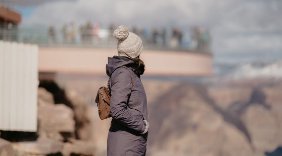 A visitor looks at the view into the canyon in front of the Grand Canyon Skywalk.